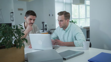 Colleagues at the workplace with computed looking on the screen. Young man professional happy and smiling. Handsome guys wearing in casual shirt. Stock Photo