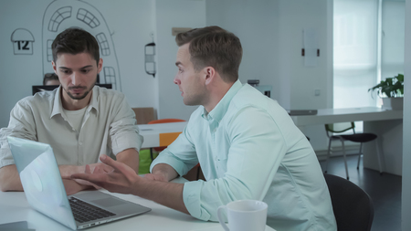 Two young professional men at the working place with computer speaking. Handsome man using laptop wearing in casual shirt.
