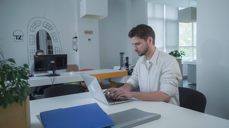 Worker using computer. Businessman typing on laptop. Young mixed race employee concentrated at the work.