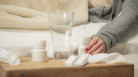 Sick girl reclining on the bed and taking medication. Washed down with water. Stock Photo - 119008269