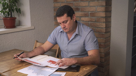 Manager sitting in the office, on the table laid out graphs and tables, the man examines the sales, behind a brick wall.