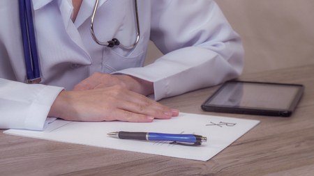 Doctor with a tablet writes in the blank. static Stock Photo - 119008506