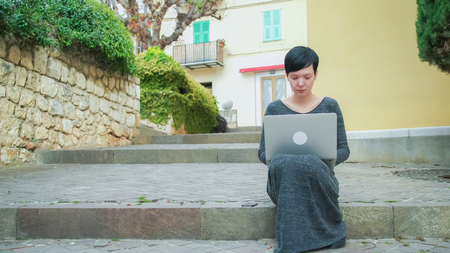 Young female checks mail on the laptop.Caucasian adult model working with pc outdoor. On the background building windows with closed shutters palm tree and green bushes.