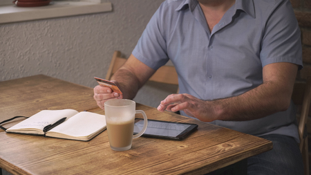 The man sitting in the cafe, pay for purchases online with credit card. On the table is a coffee and a notebook lies. Soft panorama
