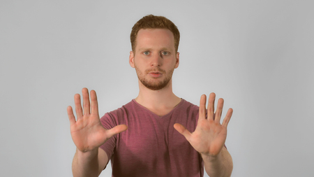 Portrait young caucasian man on grey background. caucasian guy with red hair posing showing hand gesture stop. handsome redhead men wearing in casual t-shirt
