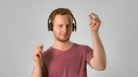 Portrait happy smiling caucasian man on grey background. caucasian guy with red hair using headphones listening music and dancing. handsome redhead men wearing in casual t-shirt