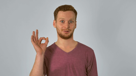 smiling caucasian guy with red hair posing showing hand gesture ok. handsome redheaded men wearing in casual t-shirt.Portrait ginger young caucasian man on grey background