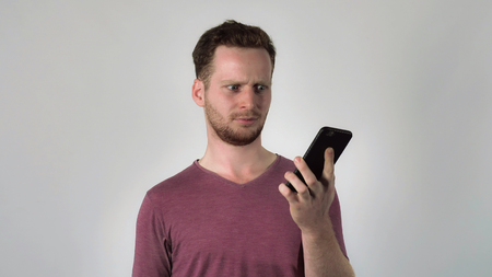 Young caucasian man has unpleasant phone conversation. angry men shouting at interlocutor. Enraged person using smartphone