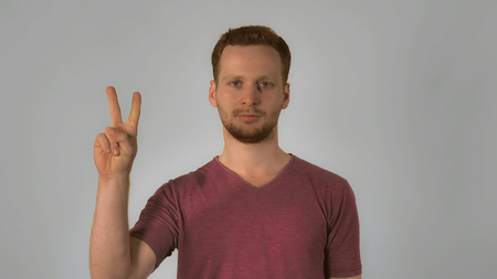 portrait happy young caucasian man on grey background chinese number gestures. caucasian guy with red hair make a gesture with the hand shows the countdown from five to start. handsome redhead men wearing in casual t-shirt Imagens