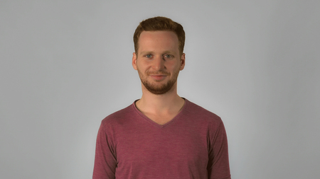 portrait happy young caucasian man on grey background. caucasian guy with red hair looks from the floor to the viewer. handsome redhead men wearing in casual t-shirt