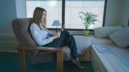Woman at home sitting on the armchair. The interior is made in Swedish style. Female talking with friend on the touch screen tablet. She smiling and  happy to see her. Long red hair cover white earphones