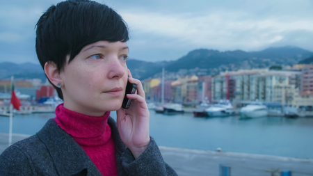 Elegant young female professional standing  seafront has conversation on the mobile phone. On the background harbour with ships and yachts. Girl in winter season dressed casual grey coat.