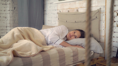woman sleeping in bedroom. Opening eyes looking at the camera with happy friendly smile. Young brunette lying in bed wearing in classic white pajamas. Morning at home. Stock Photo