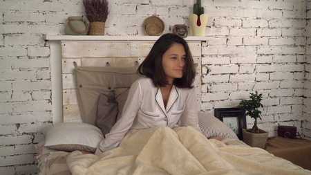 lovely woman awake and sitting on a bed in loft bedroom.Attractive girl rejoices in the morning at home. Young brunette wearing in white sleepwear smiling and stretching.