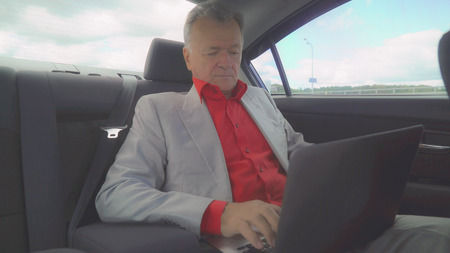Successful elderly businessman typing on computer rides in car on the meeting. Old - aged boss computing or surfing internet or working with documents on the way to work wearing in elegant suit and red shirt.Urban city view with road and sky. By him ride different cars. A stream of heavy traffic in the town.