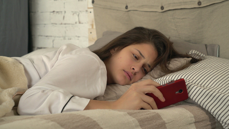 Portrait adult woman sleeping in the bed. Pretty girl waking up and looking on screen smartphone. Lady with happy smile looking at the camera in bedroom in the morning. Stock Photo