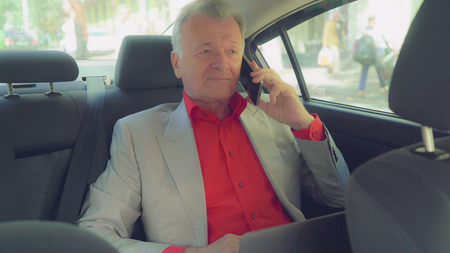 Portrait middle aged man talking on the smartphone. Professional businessman in years wearing in elegant suit speaking on the mobile phone driving on car. Male sitting on the back seat smiling with friendly smile. We can see people who walking in the city and road with different cars.