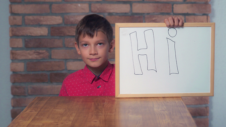 child climbs under the desk holding flipchart with lettering hi the background red brick wall. Schoolboy shows hand gesture hello. Preadolescent wearing in casual red shirt.