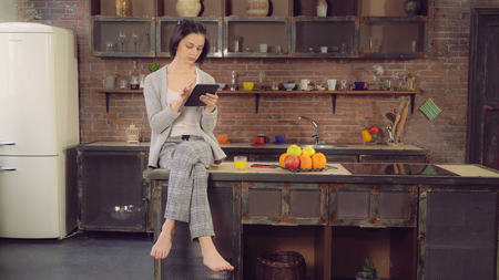 Pretty woman sitting in the kitchen. Attractive lady using touch screen tablet reads mail or news or surfing internet at home. Brunette model wearing in sleepwear. On the table glass with orange juice.