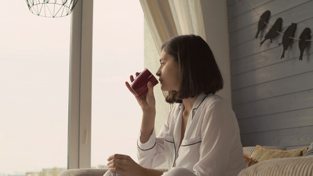 Portrait woman sitting near the big window holding red cup. Lady wearing in white pajamas sits in chair looking on the street and dreams. Young female relish drink and calm. Happy morning at home alone.