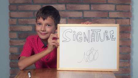 Portrait little boy showing whiteboard with handwriting word signature Child put a signature. Preadolescent wearing in casual red shirt. Schoolboy with happy friendly smile. Stock Photo