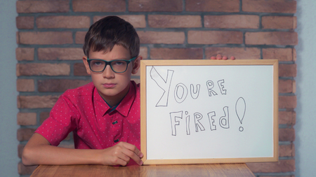 Portrait little boy showing whiteboard with handwriting word you are fired. Child with spectacles on strict face. Preadolescent wearing in casual red shirt. Schoolboy with happy friendly smile. Stock Photo