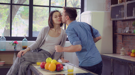 happy family on the kitchen in the morning. Young couple in love drinking orange juice at breakfast at home. Attractive woman sitting and talk with handsome man. Guy late for meeting take coffee cup and go away. Cute girl wearing in pajamas husband wearing in casual shirt and jeans. Beautiful couple kissing say goodbye.