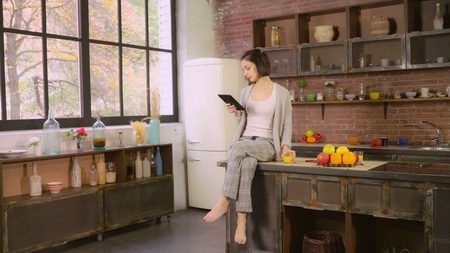 Girl drinking orange juice and reading magazine on the touch screen tablet. Attractive woman enjoy breakfast on the kitchen. Female sitting at loft room near big window at home. She using modern device and surfing internet or chatting in social net. Caucasian model wearing in sleepwear holding glass with delicious drink. Stock Photo