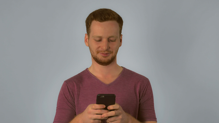 caucasian young man using smartphone. happy smiling student texting or chatting with friend via internet. handsome redheaded men wearing in casual t-shirt. Portrait ginger young caucasian man with smart phone on grey background