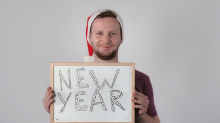 young caucasian man wearing santa hat for christmas holding whiteboard with handwriting words new year. Portrait handsome guy celebrating winter holidays