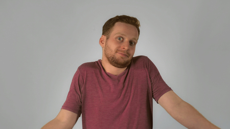 caucasian guy with red hair showing emotion surprise and misunderstanding. handsome redheaded men wearing in casual t-shirt. Portrait ginger young caucasian man on grey background