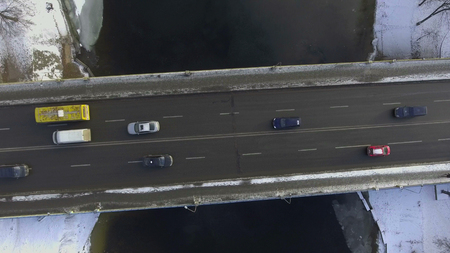 Aerial urban view in winter season. Bridge with driving cars. River with white snow. Near the shore float ducks