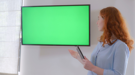 Redheaded manager standing near display with green screen on the wall. Businesswoman holding digital tablet. Female showing on the monitor.