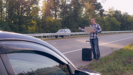 Caucasian man standing on the road with suitcase on the background broken car. Businessman wearing casual dress holding cardboard with word airport. to hitchhike Stock Photo