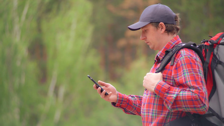 Caucasian man hiker with rucksack using smartphone looking road on on map. Handsome climber tourist in forest. Adult male in expedition wearing red shirt and cap.