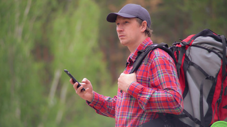 portrait hiker using smartphone. Backpacker caucasian man holding mobile phone looking on screen choose right road on map. Climber enjoy adventure and active lifestyle with modern device. Reklamní fotografie