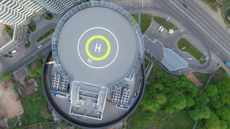 Aerial shot on the helipad. Top view on the urban landscape in the city with cars rides on the road, modern buildings and green trees.