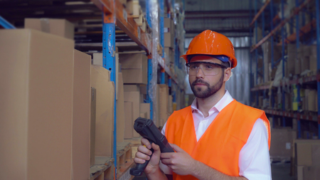manager using wireless barcode scanner scanning labels on boxes before delivery in logistic center. Handsome professional worker wearing uniform white shirt high visibility orange hard hat and vest.