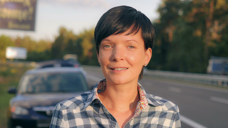 Portrait young brunette beside road. Happy smiling woman with short haircut looking at the camera with friendly smile.