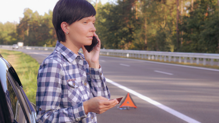 Young woman standing on the driveway near broken car holding card and mobile calling local garage or mechanic. Caucasian young female talking by smartphone on the roadside.