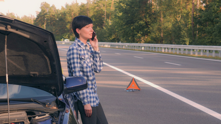 Young woman standing near broken car on the road. Caucasian brunette using smartphone calling for help. Attractive girl interrupted the trip because of a breakdown