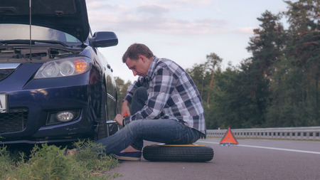 Man stuck on the side of the road with a flat tire. Caucasian driver change a tire at the roadside.