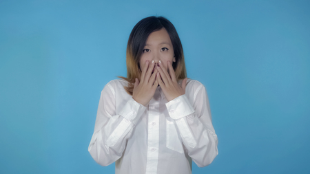 young asian woman posing showing feeling of fear on blue background in studio. attractive millennial girl wearing white casual shirt looking at the camera 免版税图像