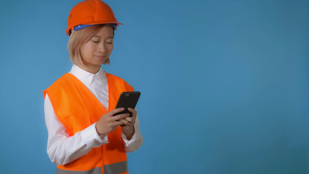 portrait young asian female posing wearing orange hard hat vest using mobile messaging or surfing internet touch screen on blue background in studio. attractive korean woman with blond hair wearing white casual shirt looking at the camera smiling