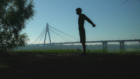 A sporty man is working out. He is holding his hands back in a lock and raises them up and down to stretch. He is training in the park with a beautiful city scale on the background.