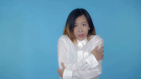 young asian woman posing freezes on blue background in studio. attractive millennial girl wearing white casual shirt looking at the camera Banco de Imagens