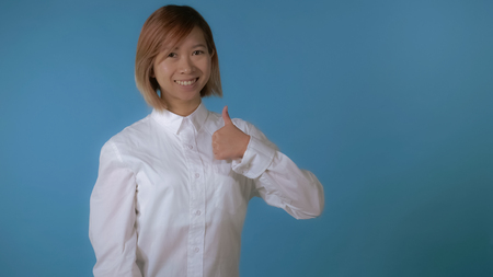 attractive korean woman with blond hair wearing white casual shirt looking at the camera smiling. portrait young asian female posing showing sign like thumbs up on blue background in studio