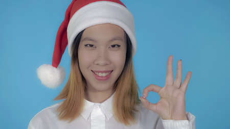 close up portrait young asian woman shows symbol okey wearing santa claus hat on blue background in studio. attractive millennial looking at the camera