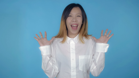 young asian woman posing showing happiness joyful mood on blue background in studio. attractive millennial girl wearing white casual shirt looking at the camera smiling