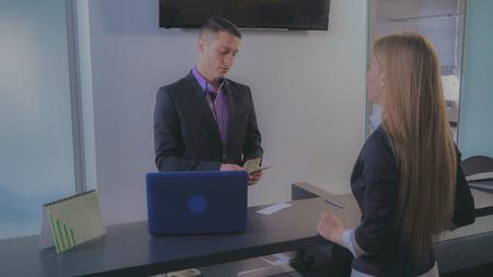 Kobieta klient gotówki czek w banku. Profesjonalny pracownik uśmiechający się dając pieniądze kobieta. Przystojny pracownik ubrany w formalny garnitur stojący przy biurku obsługi w pomieszczeniu.